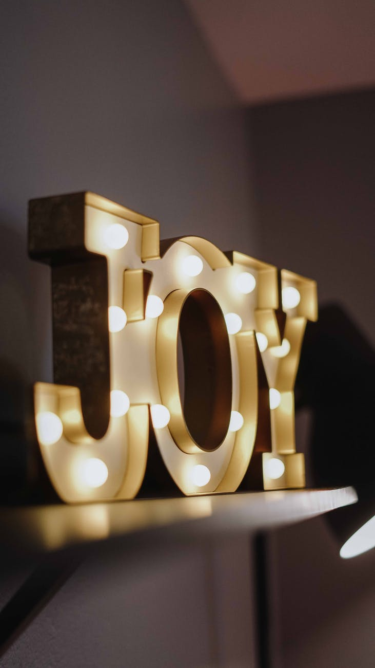 selective focus photography of joy free standing letters with lights