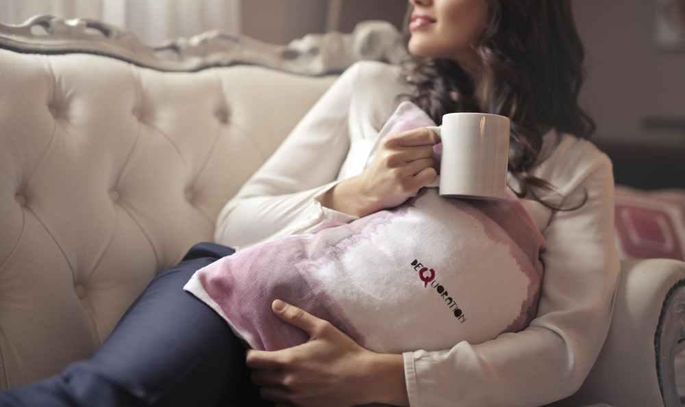 woman in white long sleeved shirt holding white ceramic mug