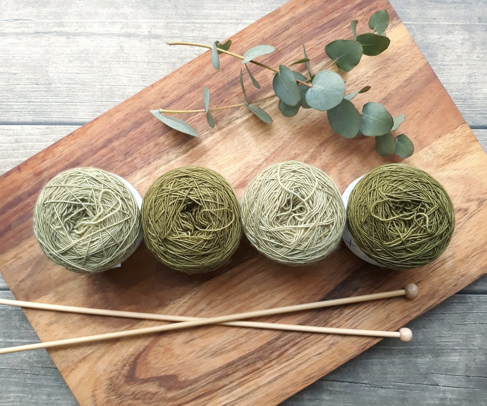 four green yarns on chopping board