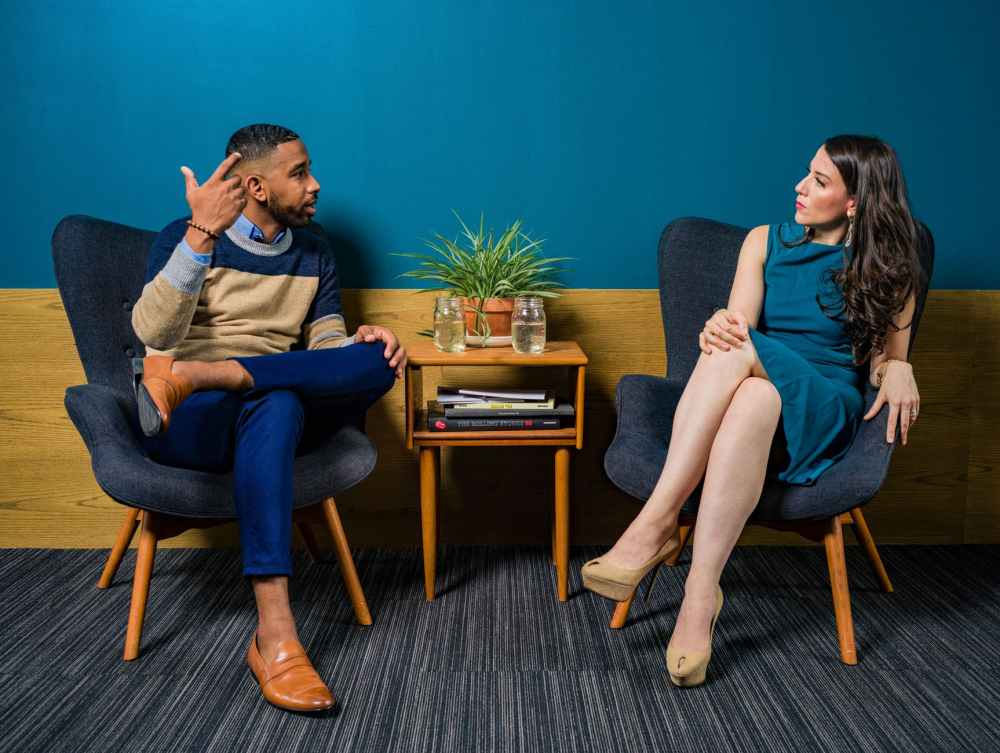 woman wearing teal dress sitting on chair talking to man